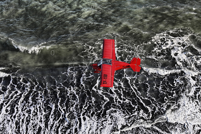 May 21, 2020: Aerial view, a red single-engine lightweight airplane flying over the waves of the North Atlantic, black lava coast, Iceland, Europe