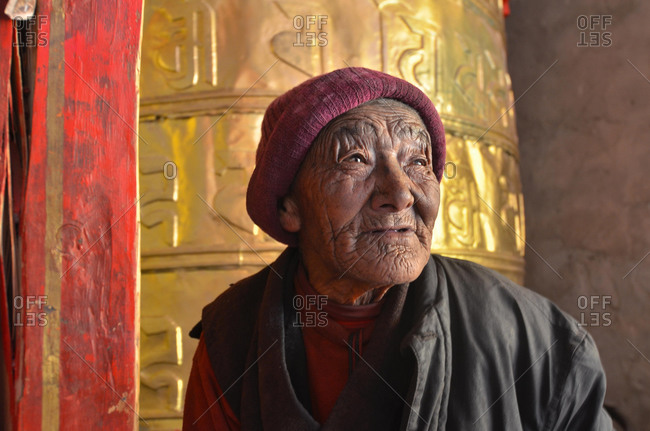 May 21, 2020: Nun, 76 years, in front of a huge golden prayer wheel, prayer cylinder, Terdrom Nunnery, Terdrom, Tidro Gompa, Himalayas, Lhundrup district, central Tibet, Tibet, China, Asia