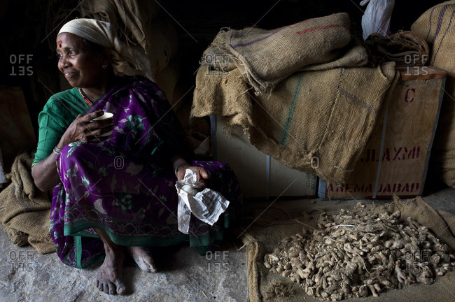 May 21, 2020: Female worker having a break and drinking tea in a ginger storage room, Jew Town, Kochi, Cochin, Kerala, southern India, India, Asia