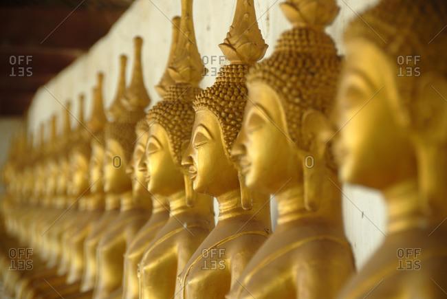 Theravada Buddhism, meditation, row of golden Buddha statues, temple, That Ing Hang Stupa, in Savannakhet, Laos, Southeast Asia, Asia
