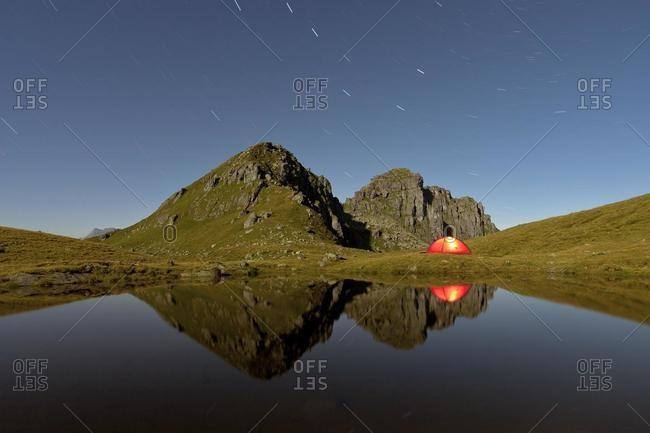 Night scene, illuminated tent beside Lake Berglimatt, Canton of Glarus, Switzerland, Europe