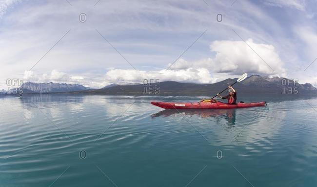 May 21, 2020: Young woman in a sea kayak, paddling, sea kayaking, mountains behind, Tagish Highland, Atlin Lake, British Columbia, Canada, America, North America