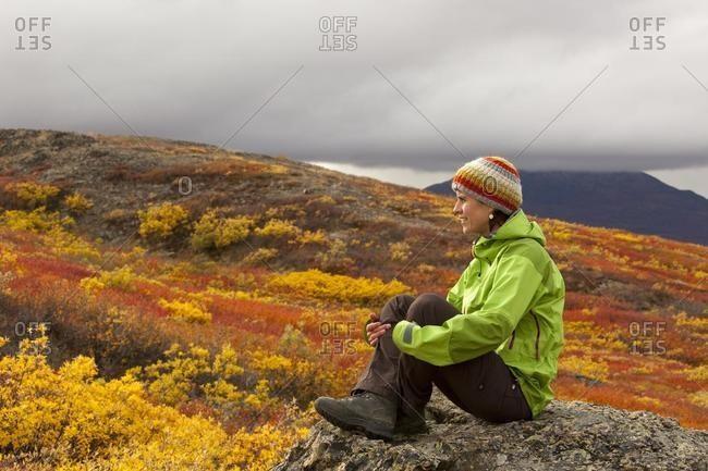 Young woman sitting on a rock, resting, enjoying view, subalpine tundra, Indian summer, autumn, near Fish Lake, Yukon Territory, Canada, North America