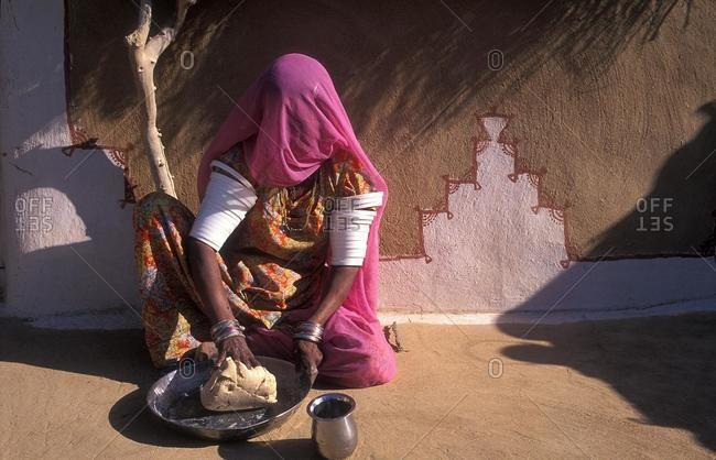 Young Indian woman in sari kneads dough for chapati bread, Thar Desert, Rajasthan, India, Asia