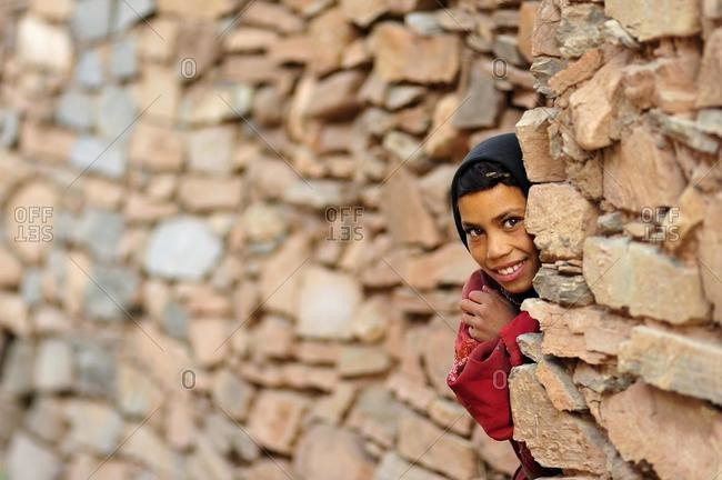 May 21, 2020: Little girl looking curiously from behind the corner of a wall, Kelaa M'gouna, High Atlas mountains, Morocco, Africa