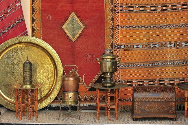 A dealer sells his goods in the souk, bazaar, carpets, brass plates, jugs and chests, Morocco, Africa