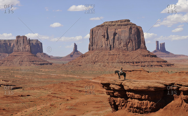 Viewpoint John Ford's Point, tourist on horseback, East Mitten Butte, West Mitten Butte, Merrick Butte, Castle Butte, Bear and Rabbit, Stagecoach, Mitchell Mesa table mountains, Monument Valley Navajo Tribal Park, Navajo Nation Reservation, Arizona, Utah, United States of America