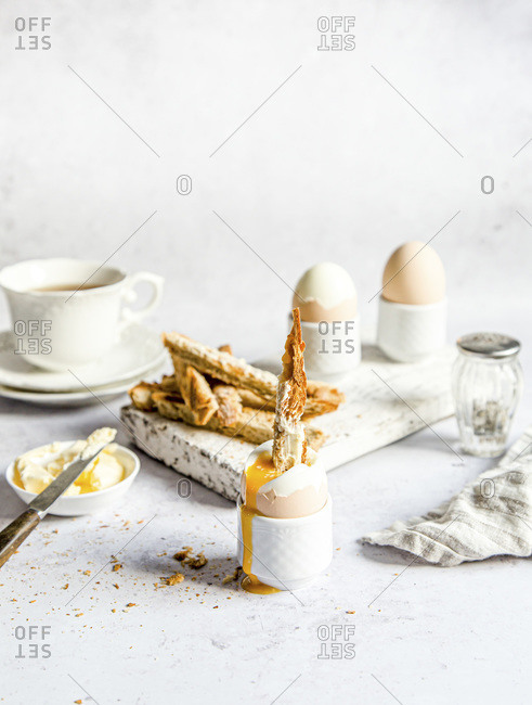 Soft boiled egg breakfast with soldiers served with coffee