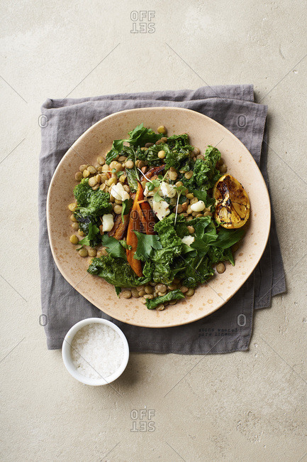 Top view image of vegetarian lunch, lentil salad with honey-roasted carrots, kale and goat cheese