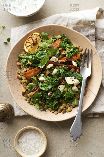 Close-up image of vegetarian lentil salad with honey-roasted carrots, kale and goat cheese