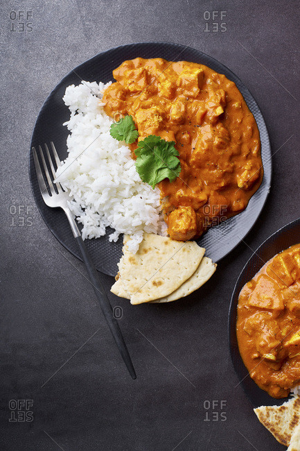 Paneer tikka masala with basmati rice. Indian cuisine, vegetarian dish made of soft cheese cubes cooked in spicy tomato sauce with cream. Top view, dark background.