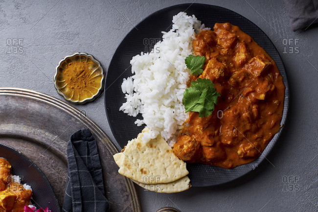 Paneer tikka masala with basmati rice. Indian cuisine, vegetarian dish made of soft cheese cubes cooked in spicy tomato sauce with cream. Top view.