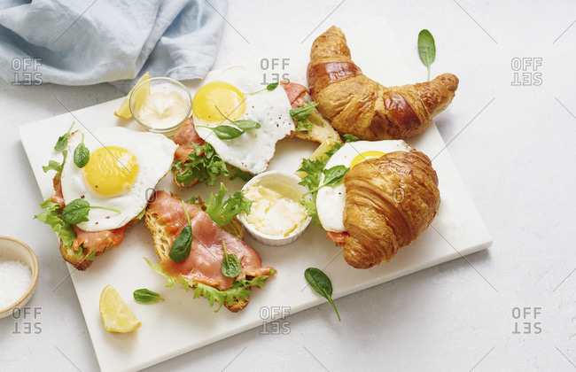 Croissants with fried egg and smoked red fish with lettuce and sauce on a marble cutting board