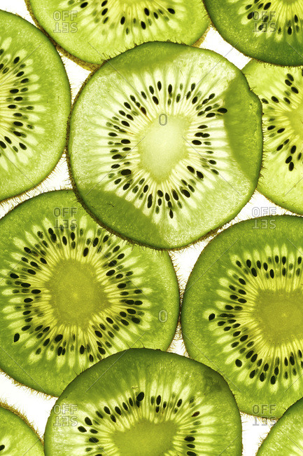 Macro shot of backlit kiwi fruit slices on white background. Top view layout