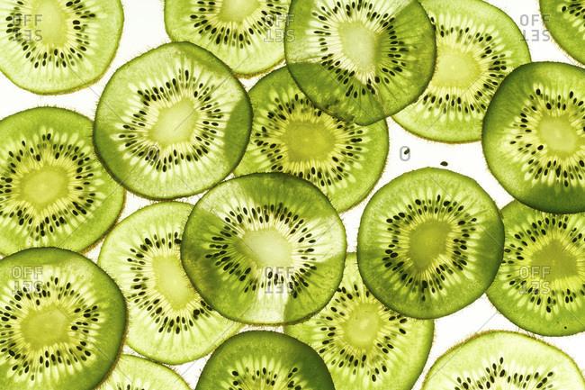 Backlit kiwi fruit slices on white background. Top view texture