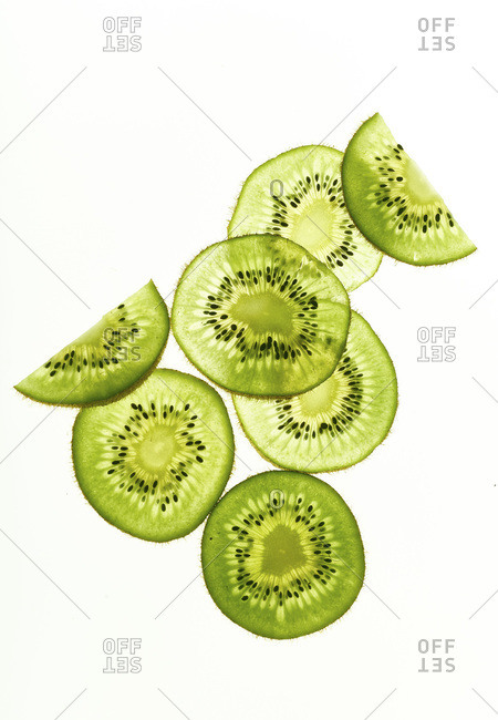 Backlit kiwi fruit slices on white background. Top view layout
