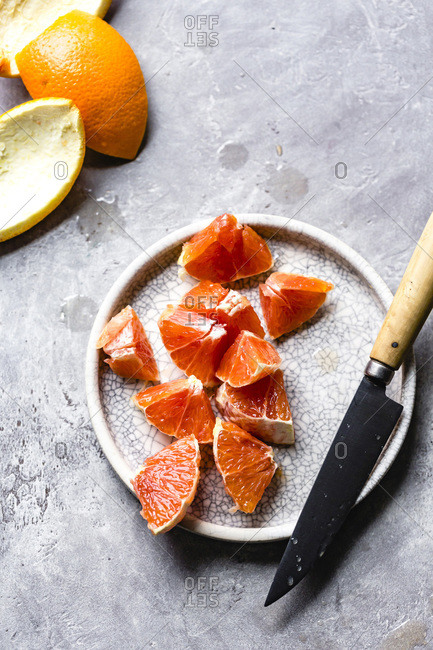 Slices of carra carra oranges on a ceramic plate.