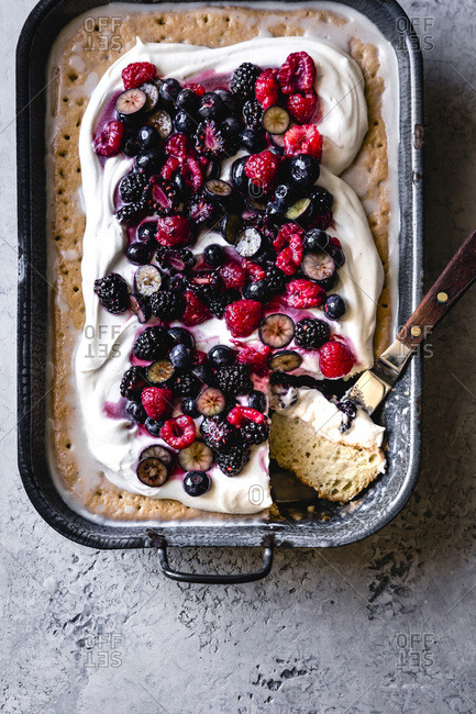 Berry tres leches cake in a baking dish.