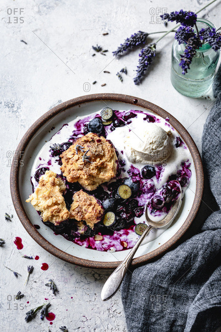 Blueberry cobbler with ice-cream in a ceramic bowl.