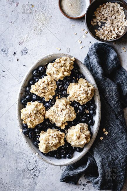 Prepared blueberry cobbler with oat biscuits ready for baking.