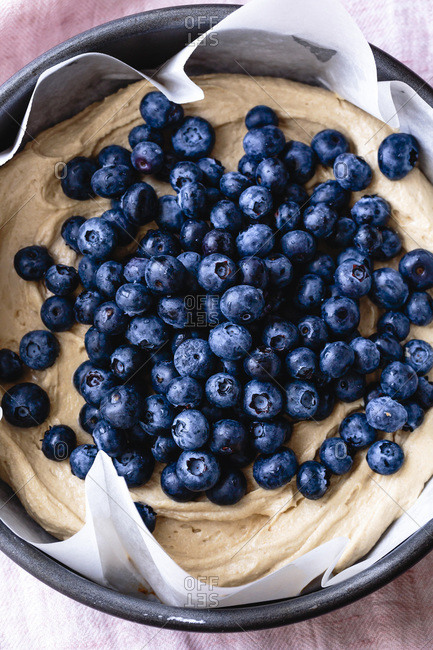 Closeup view of blueberries on cake batter in a paper lined baking tin.