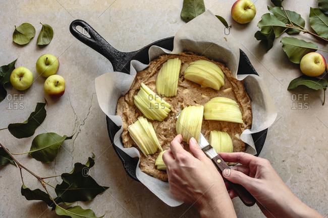 Sliced apple wedges being placed on top of apple hazelnut skillet cake batter.