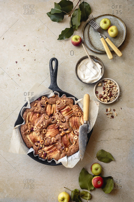 Apple hazelnut skillet cake with a knife and serving plates.