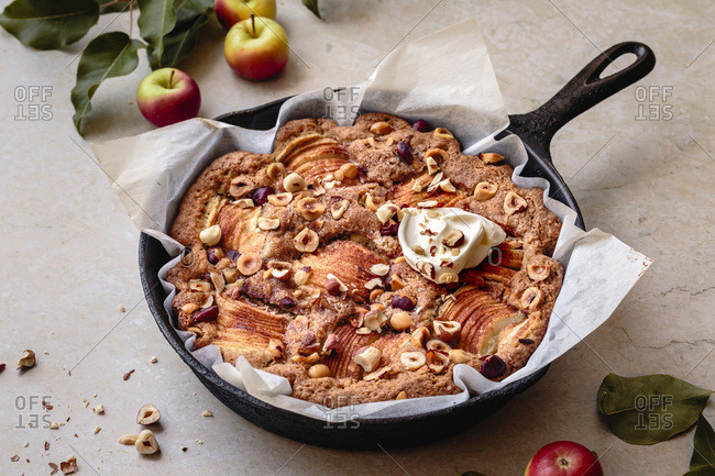 Apple hazelnut cake baked in a paper lined skillet.
