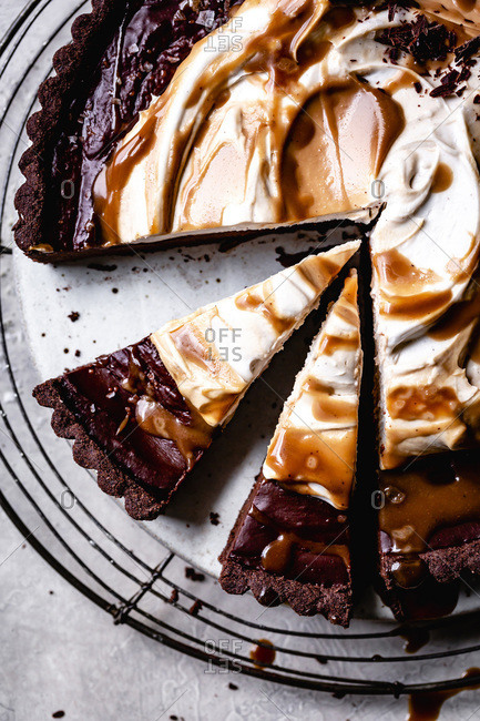 Slices of chocolate caramel tart with whipped coconut cream closeup.