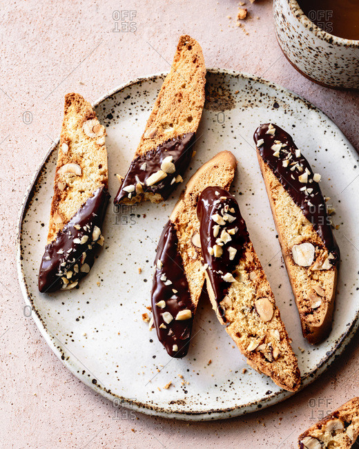 Chocolate dipped hazelnut biscotti on a ceramic plate.