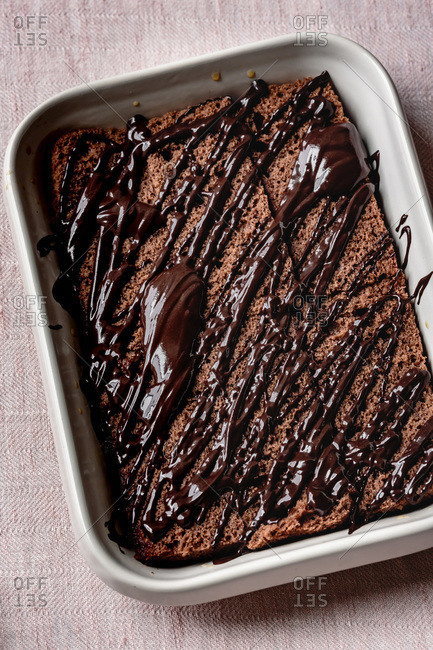 Chocolate cake in a baking dish with drizzled melted chocolate.