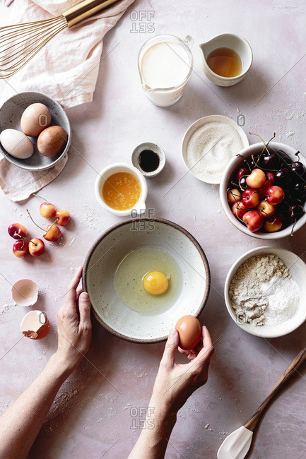 Ingredients for cherry clafoutis with a hand cracking an egg into a bowl.