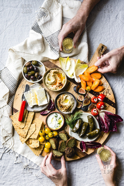 Mediterranean mezze platter with hands selecting food and holding a glass of wine.