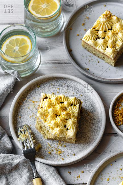 Servings of lemon sheet cake on ceramic plates.