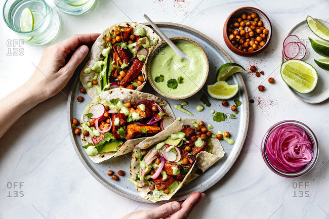 Sweet potato chickpea tacos with cilantro crema on a hand held plate.
