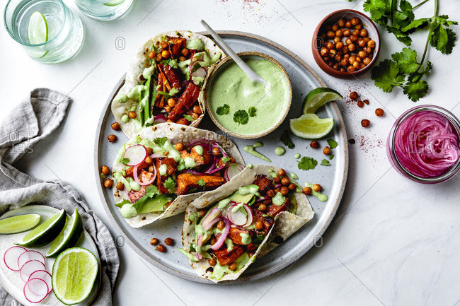 Sweet potato chickpea tacos with cilantro crema on a plate.