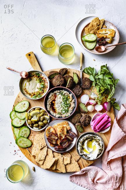 Mediterranean mezze platter with glasses of white wine.