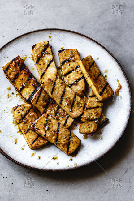 Grilled marinated tofu on a plate.