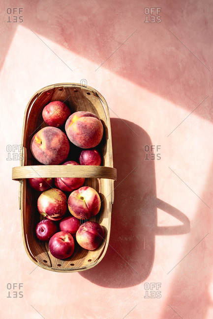 Nectarines and peaches in a basket on a pink background.