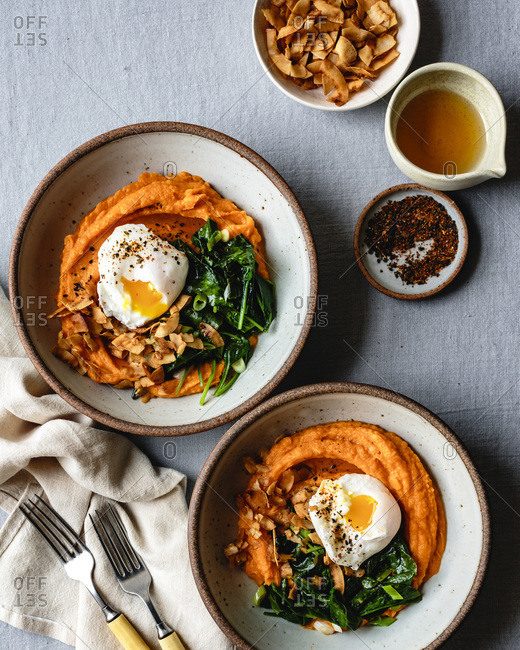 Sweet potato breakfast bowls with spinach, coconut bacon, a poached egg and sesame oil.