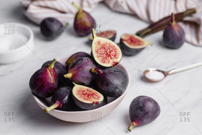 Close up of a bowl of ripe, purple figs on a white marble countertop surrounded by a striped napkin, and a rose gold spoonful of sugar