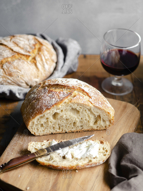 A homemade loaf of bread, sliced and buttered on a wood cutting board sitting atop a rustic table with a glass of red wine in the background