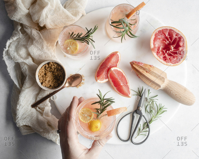 Overhead shot a hand reaching for a glass of grapefruit cocktail on a round platter with rosemary and grapefruit slices and a cup of brown sugar with a rose gold spoon