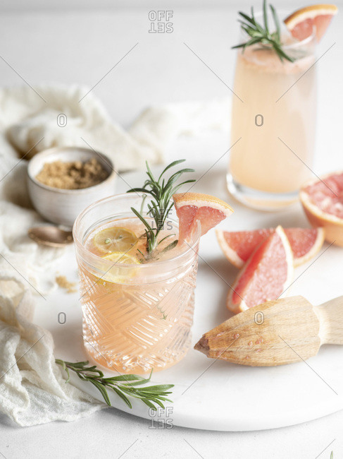 Old fashioned drinking glass filled with a grapefruit juice cocktail and garnished with lemon and rosemary on a white tray with a wooden hand juicer