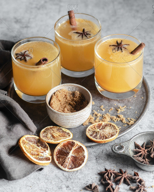 Three glasses of an orange spiced drink on a silver tray, garnished with star anise and cinnamon sticks and surrounded by blood oranges, brown sugar, a grey napkin, and sliced blood oranges