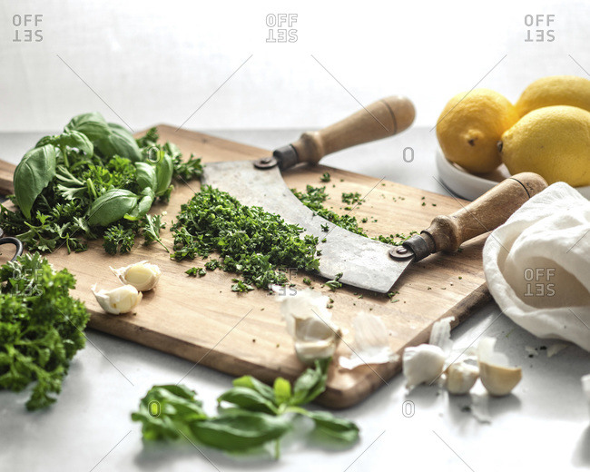 A knife with two handles resting in a pile of minced, green herbs on a wood cutting board, surrounded by lemons, cloves of garlic, and a white napkin
