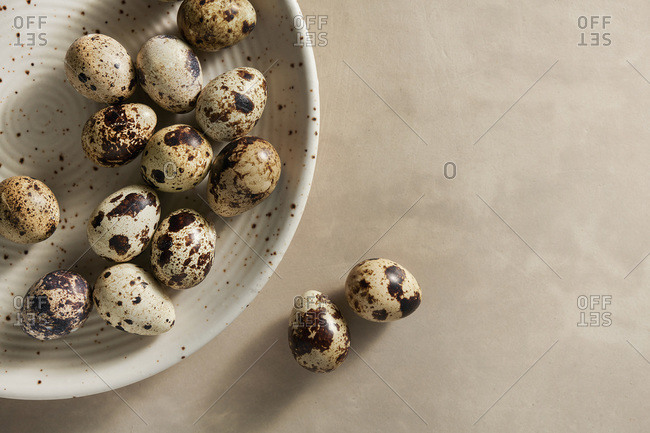 Quail eggs on a brown, speckled plate with  loose eggs on a tan background.