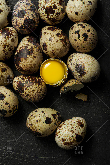 Quail eggs on a black rustic surface with one cracked open to show raw yolk inside.