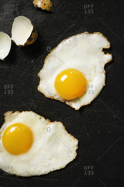 2 fried quail eggs on black cooktop surface with cracked egg shells to the side.
