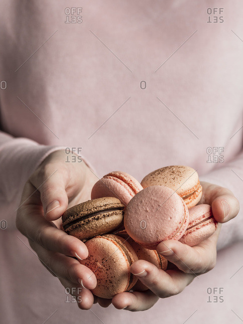 Heap of French macarons in hands of woman dressed in pink clothes. Vertical. Copy space
